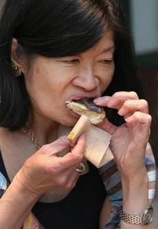 The Boston Harbor Association's Vivien Li samples a doughnut.